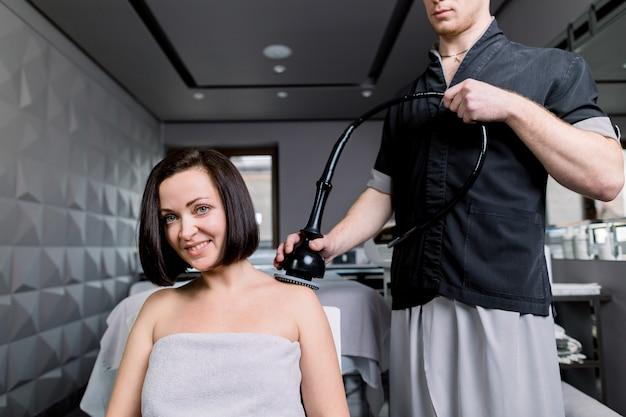 Закройте вверх молодой усмехаясь темной с волосами женщины получая профессиональный подниматься радиочастоты, лимфодренажный массаж.
