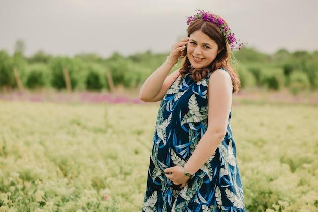 フィールドに立って、カメラ目線のマタニティを楽しんでいる頭に野生の花を持つ若い笑顔の妊娠中の女性のクローズ アップ