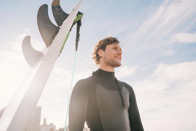 그의 서핑 보드 옆 해변에 서있는 젊은 서퍼의 클로즈업. 스포츠 및 수상 스포츠 개념.