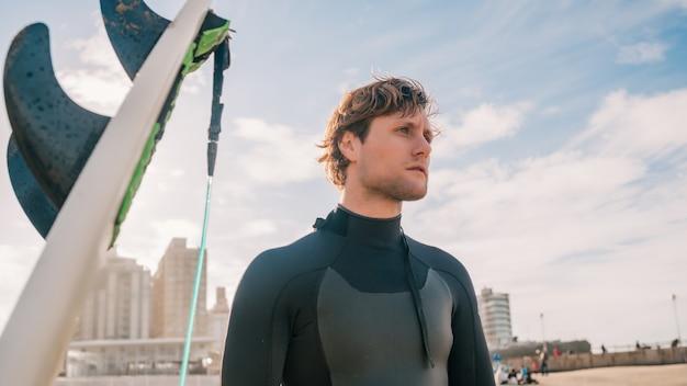 Крупный план молодого серфера, стоящего на пляже рядом со своей доской для серфинга. концепция спорта и водных видов спорта.