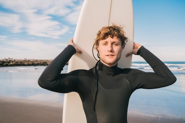 Крупный план молодого серфера, стоящего на пляже со своей доской для серфинга и в черном костюме для серфинга. концепция спорта и водных видов спорта.