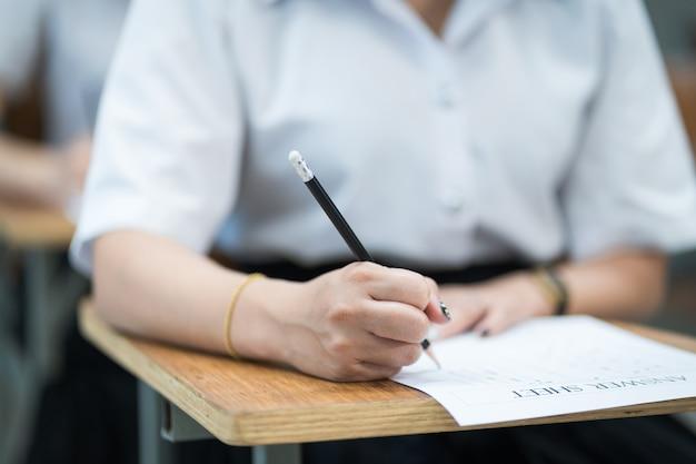 Крупным планом молодых студентов университета сосредоточиться на сдаче экзамена в классе. студентка пишет на экзаменационных листах для ответов в классе.