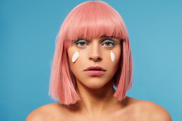 悲しいことにカメラを見て、青い背景の上に分離された涙の代わりに彼女の頬に白い花びらを持っている短いピンクのヘアカットを持つ若い動揺した緑色の目のきれいな女性のクローズアップ