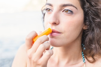 Close-up of young woman applying lip balm