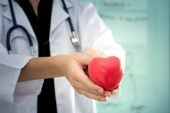Close up of young woman doctor holding a red heart