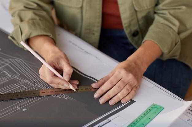 エンジニアのオフィスのデスクで作業しながら青写真と計画を描く若い女性のクローズアップ