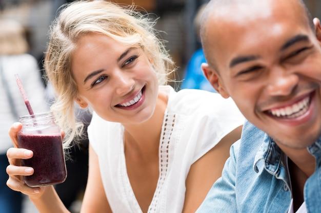 コーヒーショップで友人と健康的なスムージーを飲む若い女性のクローズアップ