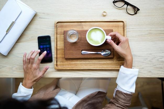 Крупный план молодой женщины, пьющей латте зеленого чая матча на деревянном столе в кафе. вид сверху.