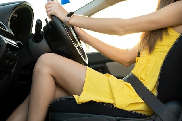 車を運転するハンドルの後ろに黄色のサマードレスを着た長い脚のシートベルトで固定された若い女性ドライバーのクローズアップ。