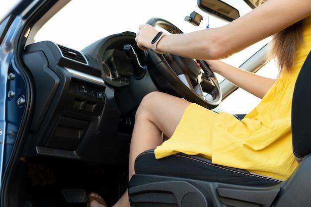 운전대 뒤에 노란색 여름 드레스를 입은 젊은 여성 운전자 다리를 닫습니다.