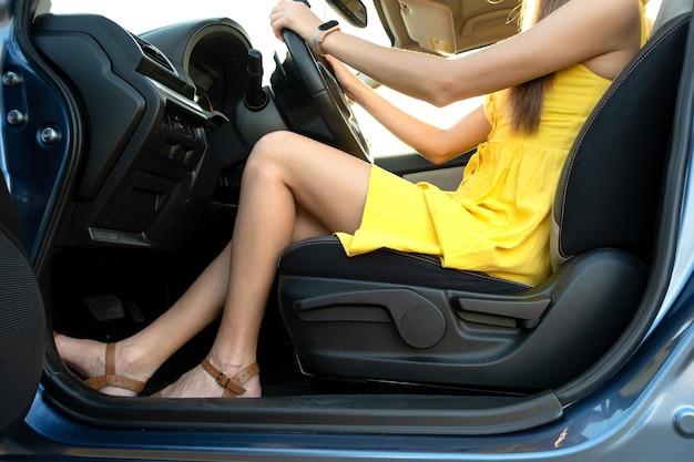 운전대 뒤에 앉아 있는 노란색 여름 드레스를 입은 젊은 여성 운전자 다리 클로즈업