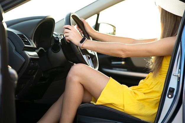 운전대 뒤에 노란색 여름 드레스를 입고 긴 다리를 가진 젊은 여성 운전사를 가까이서 보세요.