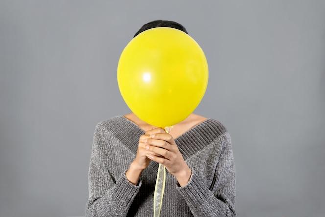회색 벽에 노란색 ballon와 함께 그녀의 얼굴을 숨기는 젊은 여자의 닫습니다. 2021 년 컬러 트렌드. 긍정적 인 개념