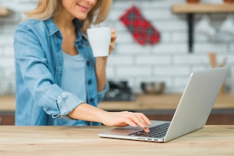 Close-up of young woman holding cup of coffee typing on laptop over the wooden table