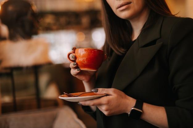 레스토랑에 서 있는 동안 맛있는 뜨거운 커피 한 잔을 손에 들고 있는 젊은 여성 클로즈업