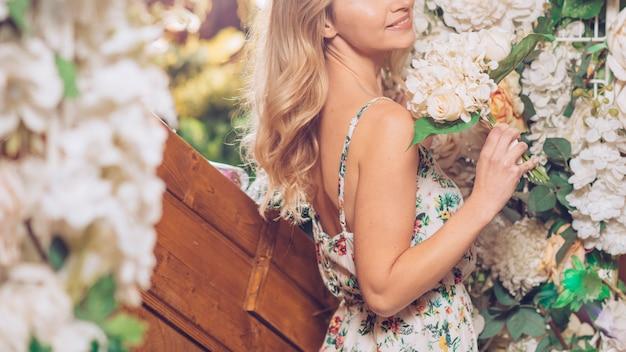 Крупный план молодой женщины, держащей букет белых цветов в руке