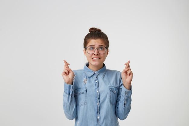 目を閉じて、手を上げて、指を交差させて立っている眼鏡の若い女性のクローズアップ