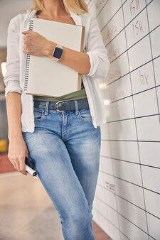 Крупным планом молодая женщина в джинсах, держащая спиральный альбом для рисования, смартфон и маркер
