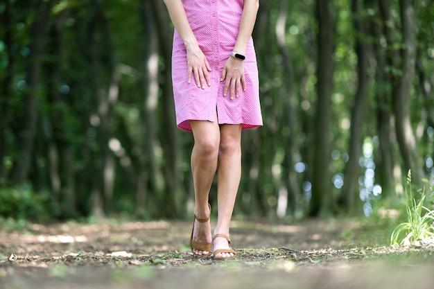 Закройте вверх молодой женщины в розовом платье с тонкими ногами, идущими на открытом воздухе в зеленом летнем парке.