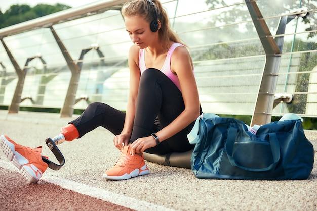 Крупным планом молодой женщины в спортивной одежде и наушниках с протезом ноги, связывающим ее Premium Фотографии