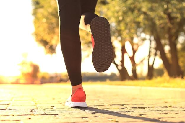 야외에서 운동하는 동안 조깅하는 운동화를 신은 젊은 여성의 클로즈업.