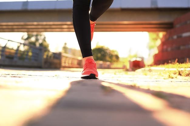 Закройте молодой женщины в спортивной обуви, бегая трусцой во время тренировки на открытом воздухе.