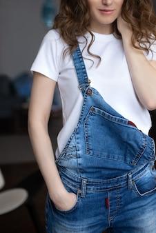 Крупным планом молодой женщины в белой футболке и джинсовом комбинезоне