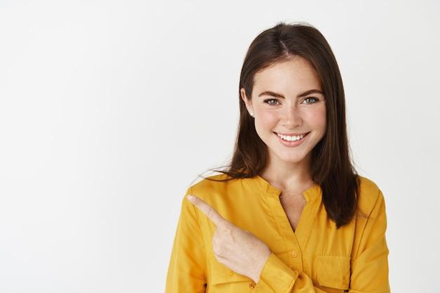 Крупный план молодой женщины в желтой рубашке, указывая пальцем влево на баннер с продуктом, улыбаясь и глядя в камеру. женская модель показывает рекламу