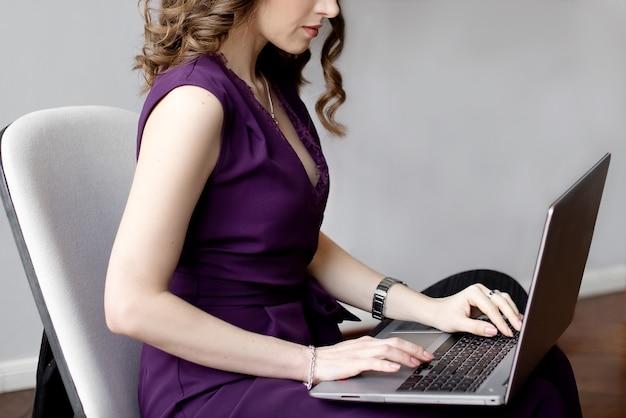 Крупным планом молодая женщина работает на ноутбуке, лежа на коленях