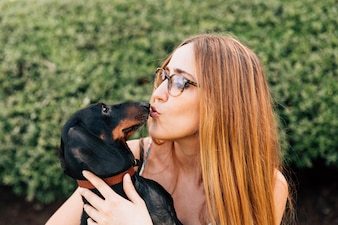Close-up of young woman kissing her lovely dog