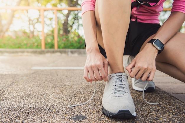 公園の中でエクササイズする準備ができている彼女の靴の上に若い女性のレースのクローズアップ