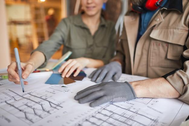 家のリフォーム、コピースペースについて話している間、建築請負業者と間取り図を見ている若い女性のクローズアップ