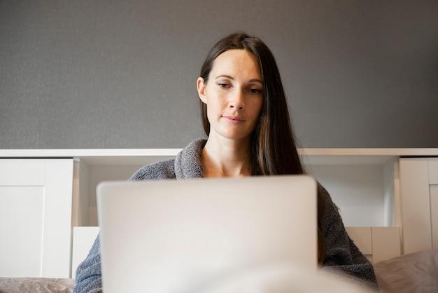 Крупный план молодой женщины или девушки, сидящей на кровати, работающей на ноутбуке, с использованием компьютера и видеочата