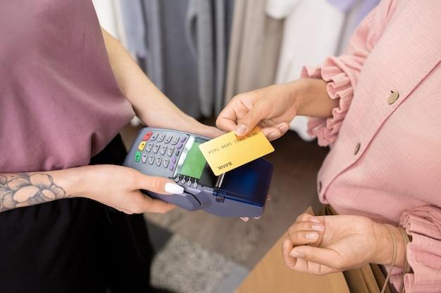 상점에서 그녀의 구매에 대해 신용 카드로 지불하는 젊은 여성의 클로즈업