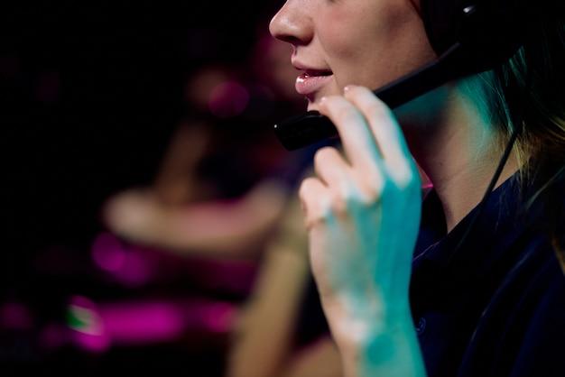 Крупный план молодой женщины, играющей в сетевую видеоигру и говорящей в микрофон гарнитуры во время обсуждения стратегии игры с членом команды