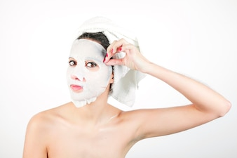 Close-up of young woman pulling white mask from face