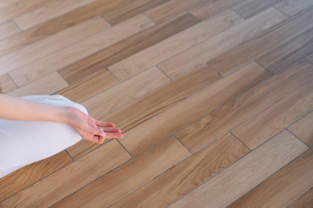 ホームオフィスの床に座って膝の上にナマステの姿勢で手を置く若い女性のクローズアップ。
