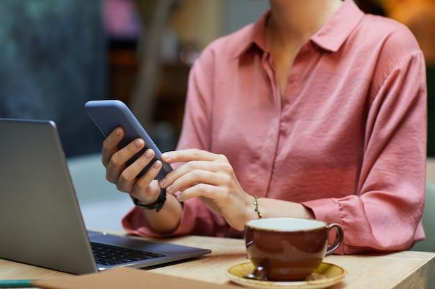 ノートパソコンとコーヒーと一緒にテーブルに座って電話でメッセージを読んでいる若い女性のクローズアップ