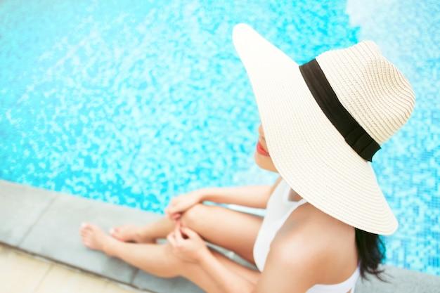 夏、選択フォーカスでプールでリラックスする若い女性のクローズアップ