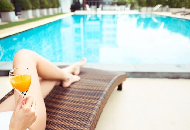 오렌지 주스, 선택적 포커스와 함께 여름에 수영장에서 편안한 젊은 여자의 닫습니다