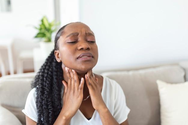 염증이 있는 편도선을 문지르는 젊은 여성의 클로즈업, 편도선염 문제, 잘립니다. 갑상선 문제가 있는 여성, 목을 만지고, 인후통이 있는 소녀