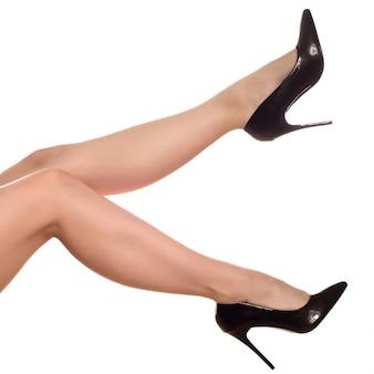 Крупным планом ноги молодой женщины в черных туфлях на высоких каблуках, изолированные на белом