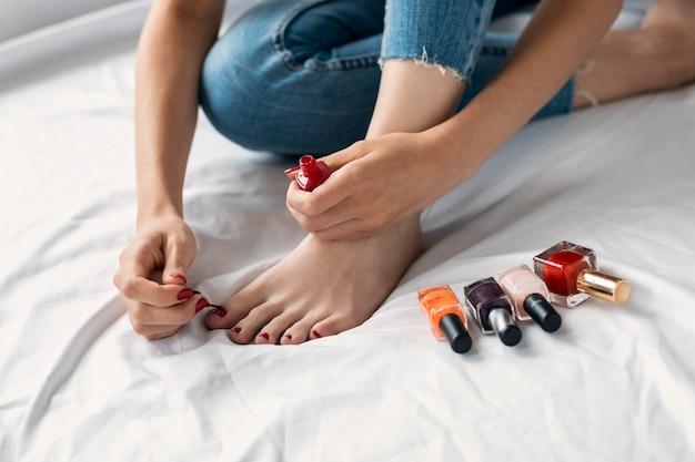 Крупным планом - молодая женщина сидит на белом диване в гостиной и красит ногти на ногах в красный цвет.