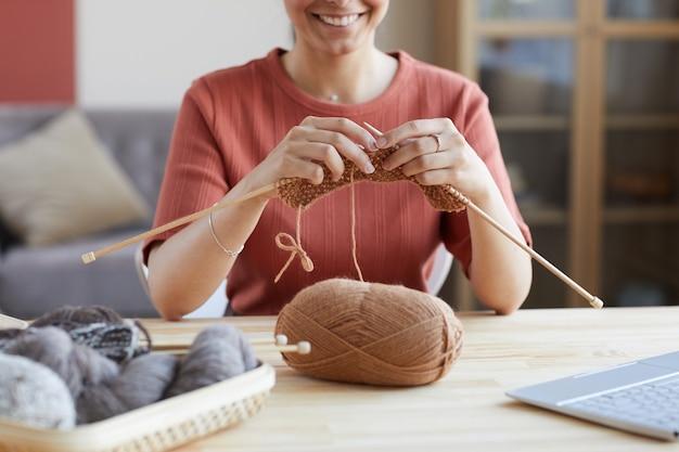 テーブルに座って、家で編み物をする若い女性のクローズアップ