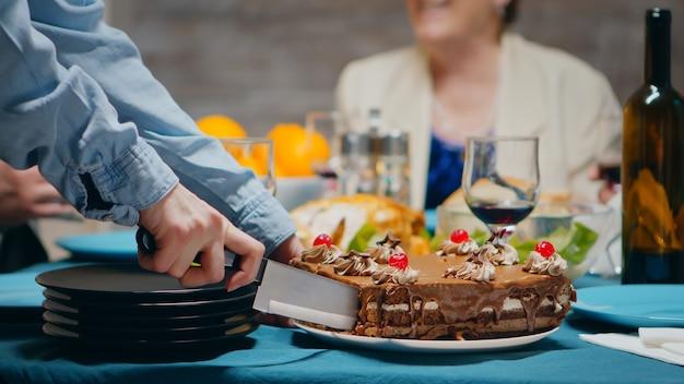 가족을 위해 생일에 맛있는 케이크를 자르는 젊은 여성의 클로즈업.