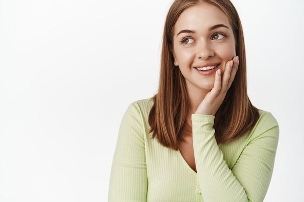 笑顔、きれいな輝く肌に触れ、プロモーションテキスト、空想、美容とスキンケアの概念、白い壁を見つめている若い女性のクローズアップ。