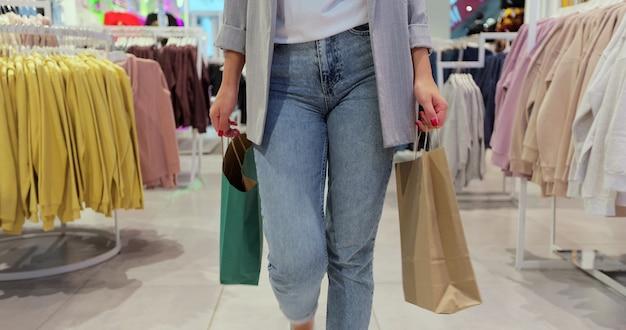 若い女性のクローズアップは、デパートの周りにカラフルな買い物袋を持って歩きます。検疫後の買い物。