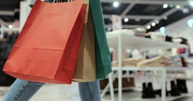 쇼핑몰 주변에 화려한 쇼핑백을 들고 걷는 젊은 여성의 클로즈업. 검역 후 쇼핑.