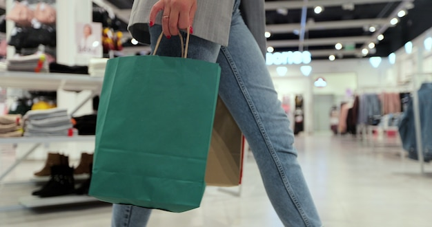 若い女性のクローズアップは、ショッピングモールの周りにカラフルな買い物袋を持って歩きます。検疫後の買い物。