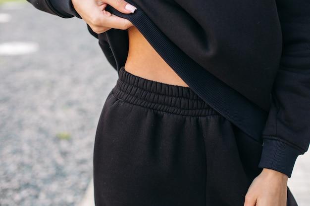 黒のトラックスーツを着て、彼女の手でパーカーを持ち上げる若い女性のクローズアップ。女性のファッション。コピースペース